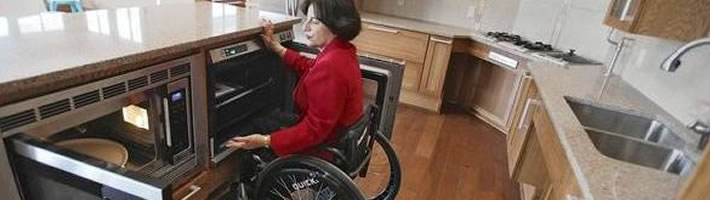 A female wheelchair user is positioned between a microwave oven on her left and a conventional oven on her right, both at an appropriate height for her to transfer cooking to or from each oven.
